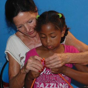 Volunteer teaching a child to knit