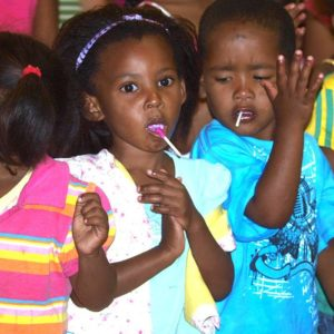 Children singing at the Crèche while eating pops