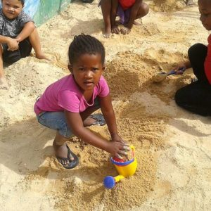 Children enjoying the sandpit in summer