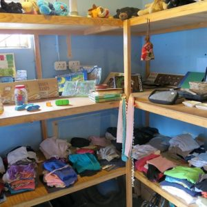 Shelves stocked with items of clothing, toys and stationery