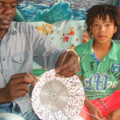 A young boy is learning the art of bead crafting