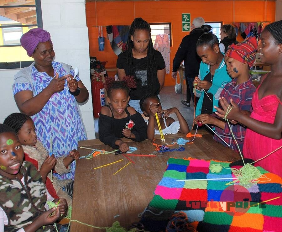 Children learning to knit blocks to make a blanket