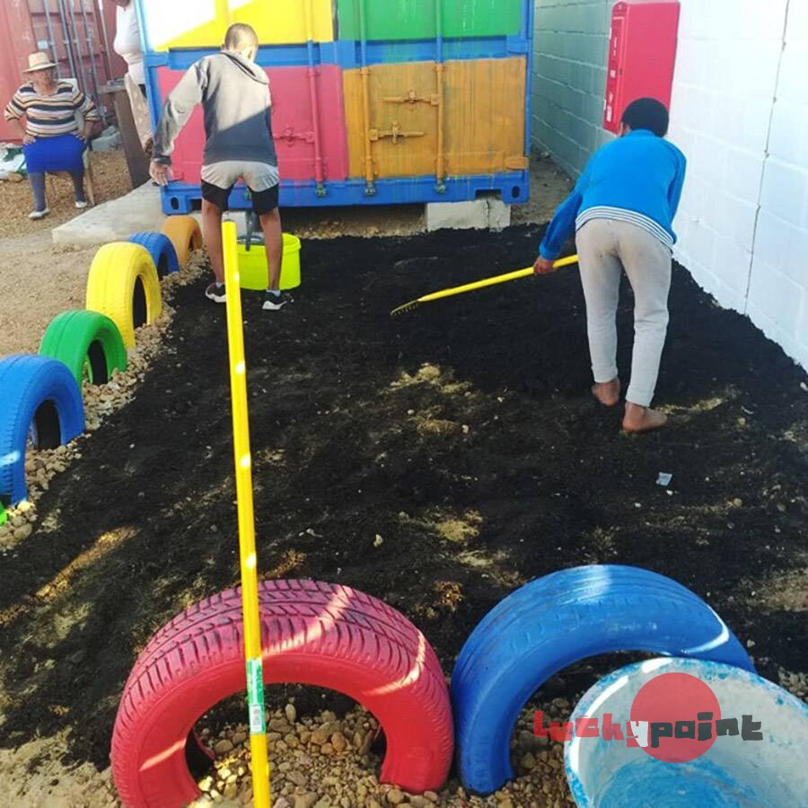 Working potting soil and fertiliser into the garden bed